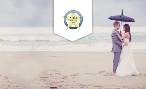 Abia winner 2012 couple on beach holding umbrella