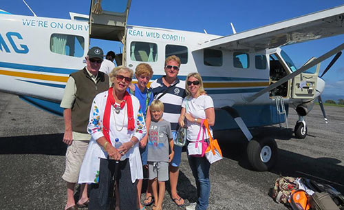 Family standing by small chartered plane