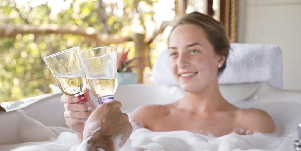 woman in bathtub drinking champagne