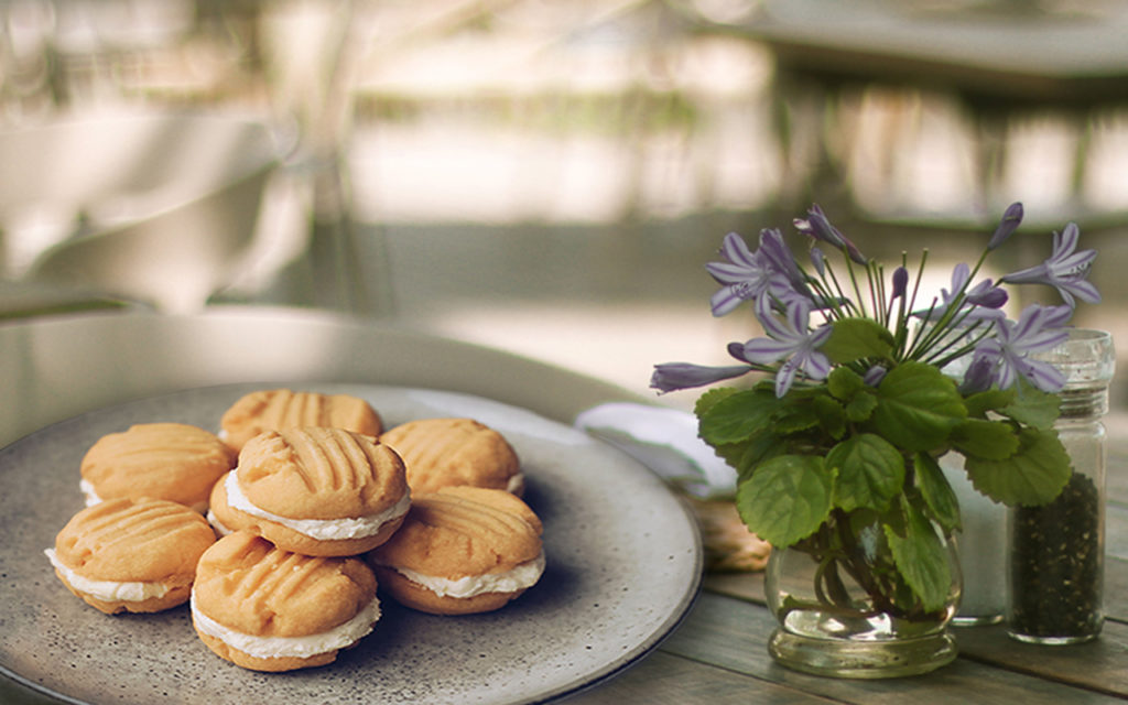 melting moment biscuits on a plate with flowers on table